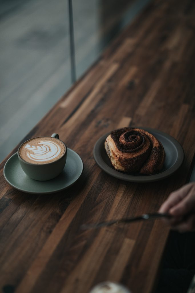 Coffee and Cinnamon Bun on a Wooden Table
